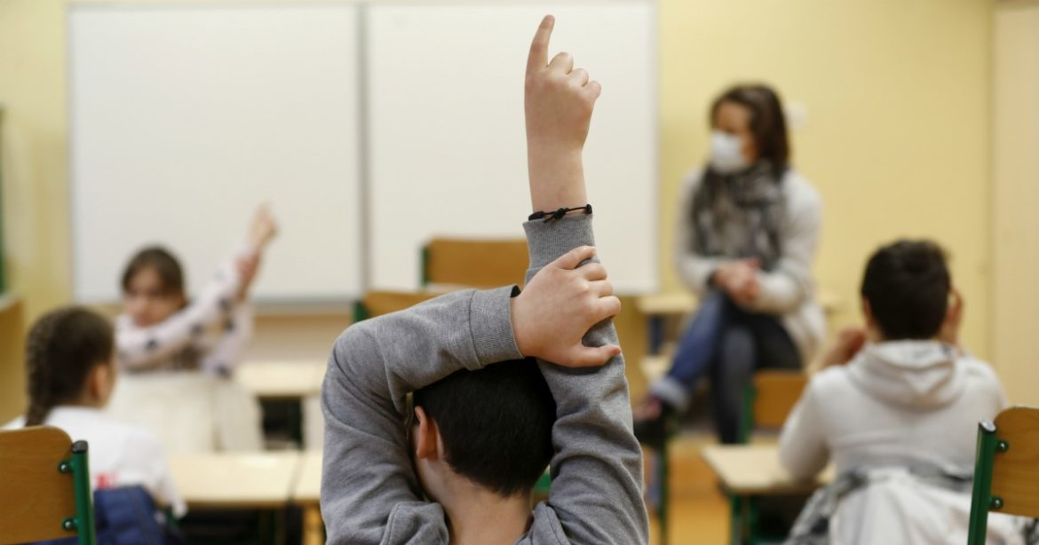 Schoolchildren raise their fingers to answer their teacher Sandrine Albiez, wearing a face masks, in a school in Strasbourg, eastern France, Thursday, May 14, 2020. The government has allowed parents to keep children at home amid fears prompted by the COVID-19, as France is one of the hardest-hit countries in the world. Authorities say 86% of preschools and primary schools are reopening this week. (AP Photo/Jean-Francois Badias)