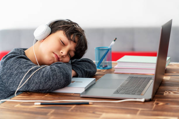 Tired Little boy get sleepy front of laptop while he is studying at home online